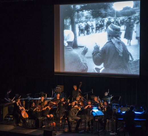 Orchestra playing in front of a screen